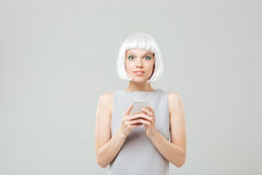 Happy cute young woman standing and using smartphone Royalty Free Stock Photo