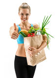 Happy cutie athletic woman gesturing thumb up with grocery bag full of healthy fruits and vegetables Stock Photography