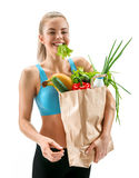 Happy cutie athletic woman with lettuce in her mouth and grocery bag full of healthy fruits and vegetables Stock Photo