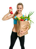 Happy cutie athletic woman showing biceps with grocery bag full of healthy fruits and vegetables Stock Image