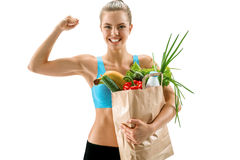 Happy cutie athletic woman showing biceps with grocery bag full of healthy fruits and vegetables Royalty Free Stock Images