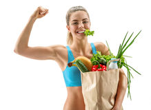 Happy cutie athletic woman showing biceps with grocery bag full of healthy fruits and vegetables Royalty Free Stock Photo
