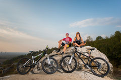 Happy cyclist couple in the sunglasses sitting on a rock Stock Images