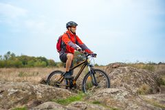 Happy Cyclist in Red Resting on the Bike on Rocky Trail. Adventure Sport and Travel Biking Concept. Royalty Free Stock Image