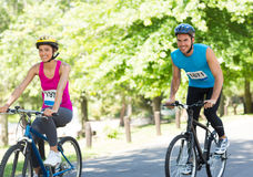 Happy cyclists riding bicycles Stock Images