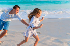 Happy dad and adorable little kid at tropical beach. Family having fun together on summer vacation on white beach. Happy father and his adorable little daughter Stock Image