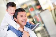 Dad carrying his son at the mall Stock Photo
