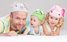 Happy dad with children. Happy dad with kids in funny hats lying on the bed stock images