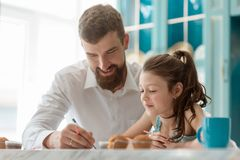 Happy dad drawing with daughter. Adults spend time with children, family education, art classes stock image