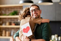 Happy dad getting congratulations from his cute daughter on Fathers day, holding greeting postcard