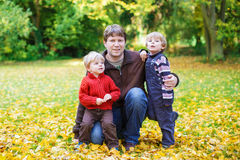 Happy dad with his little sons having fun on sunny autumn day in Royalty Free Stock Image