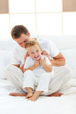 Happy dad and his son playing together. On a bed Royalty Free Stock Photos