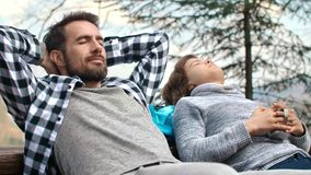 Dad and his teenage son with closed eyes relaxing outdoors. Happy dad and his teenage son with closed eyes relaxing outdoors stock video
