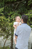 Happy dad holding his son. Portrait of dad holding his son by the arm laughing in a park Stock Photo