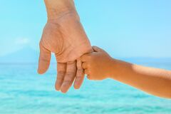 Happy Dad Holds The Hand Of A Child By The Greek Sea In Nature Royalty Free Stock Photography