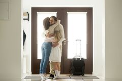 Happy dad hugging family arriving home, welcome home father conc. Happy dad hugging family tight arriving from long business trip with suitcase, smiling loving royalty free stock photography