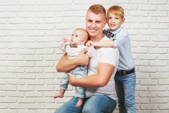 Happy dad hugging his two sons. On the background of brick wall Royalty Free Stock Photos