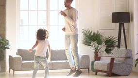 Happy dad and kid daughter laughing jumping dancing in living room