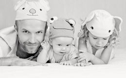 Happy dad with kids in funny hats. Lying on the bed ( black and white Royalty Free Stock Photography