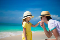 Happy dad kisses the hand of his little daughter on beach Stock Image