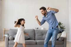 Happy dad and little daughter laughing dancing in living room