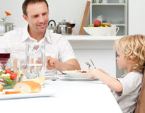 Happy Dad Looking At His Son Eating Pasta Royalty Free Stock Images
