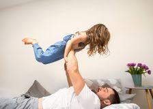Happy dad playing with his daughter at home, father`s day stock images