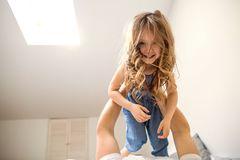 Happy dad playing with his daughter at home, father`s day stock photo