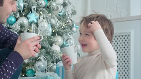 Happy dad and son with cups of tea talking near Christmas tree at home. Closeup shot. Professional shot on BMCC RAW with high dynamic range. You can use it e.g Stock Photos