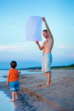 Happy dad and son flying fire lantern together Royalty Free Stock Image