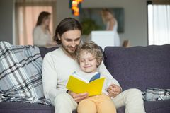 Happy dad and little son reading book together at home. Happy dad and son having fun with book together, loving daddy teaching preschool boy to read, daddy Stock Photo