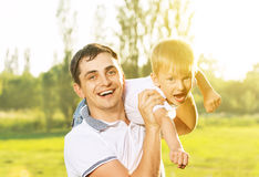 Happy Dad and son hugging, playing and laughing in summer nature. Happy family in summer nature. Dad and son hugging, playing and laughing Stock Photos