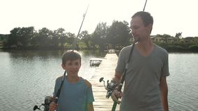 Happy dad and son with rods going fishing on pond stock video footage