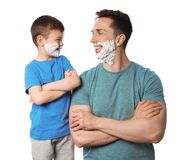 Happy dad and son with shaving foam on faces against white stock image