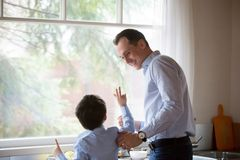 Happy dad and son having fun in kitchen together. Happy dad and son spend time at home enjoying weekend together, smiling father and kid cooking food or washing royalty free stock photos