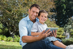 Happy dad and son with a tablet pc Stock Photography