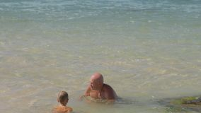 Happy dad spends time with little son in warm sea at resort. Happy careful daddy spends time with funny little son in warm sea water at tropical summer resort stock video