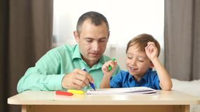 Happy dad spends time playing and drawing with his little son.
