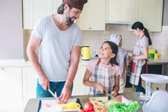 Happy dad stands with his daughter and cuts vegetables. They look at each other and smile. Mom workswith son behind them. At stove Royalty Free Stock Photo