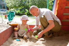 Happy dad with toddler. Playing with sand in sandbox royalty free stock photography