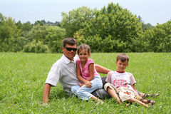 Happy daddy with children. The happy daddy sits on a grass with children Royalty Free Stock Photo
