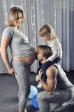 Happy daddy with daughter on his shoulders kissing his wife's belly Stock Images