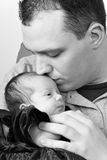 Happy Daddy Kissing His Baby. A newborn baby girl being by her dad as he kisses her head in black and white Stock Photos