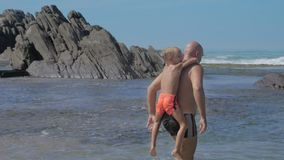 Happy daddy walks with boy on back along empty ocean beach
