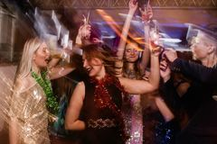 Happy dance at night club in blurred motion. Joyful friends at Christmas discotheque, active New Year company with drinks, modern youth life Royalty Free Stock Images