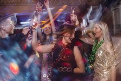 Happy dance at night club in blurred motion. Joyful friends at Christmas discotheque, active New Year company with drinks, modern youth life Royalty Free Stock Photos