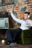 Happy dancing man in big headphones listens old radio Stock Photos