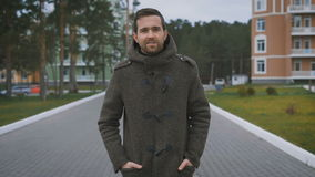 Happy dark-haired man with beard in brown coat walking along the street with orange and blue buildings and trees in the. Happy dark-haired man with beard dressed stock footage