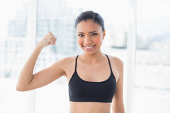 Happy dark haired model in sportswear contracting her muscles Royalty Free Stock Photo