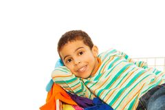 Happy dark skinned boy in clothes basket Royalty Free Stock Images